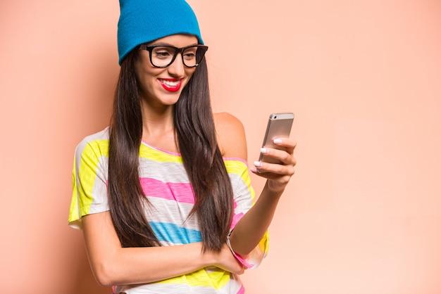 Donna alla moda felice in vestiti colorati facendo uso dello smartphone.