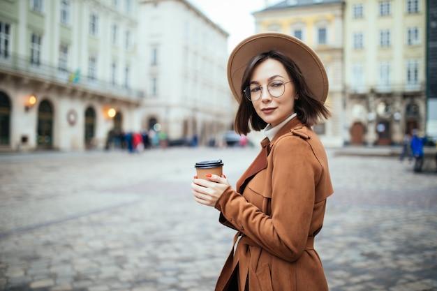 Donna alla moda in cappello largo che beve caffè sulla città di autunno