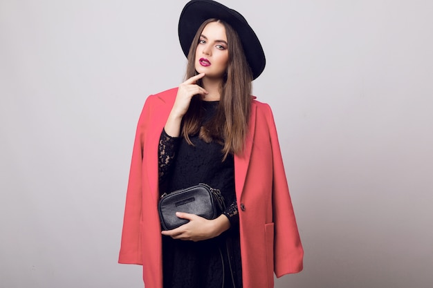 Donna alla moda in cappotto rosa e cappello nero in posa