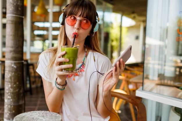 Donna alla moda in occhiali rosa godendo frullato sano verde, ascolto musica da auricolari, in possesso di telefono cellulare.