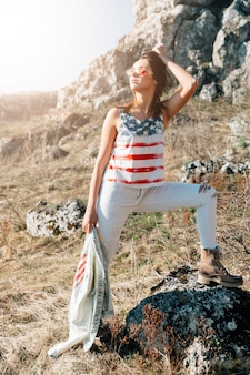 Donna alla moda in piedi sulla pietra con giacca di jeans