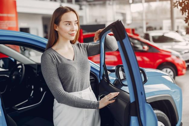 Donna alla moda in un salone di auto