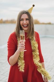 Donna alla moda in vestito rosso che tiene un bicchiere di champagne e sorridere
