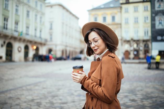 Donna alla moda in vetri che beve caffè sul fondo della città di autunno