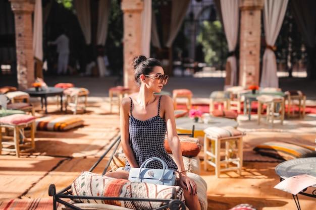 Donna alla moda su una terrazza in estate