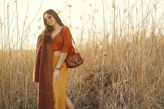 Donna alla moda trascorrere del tempo in un campo estivo