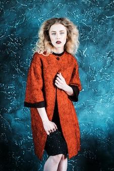 Donna alla moda vestita con un cappotto rosso