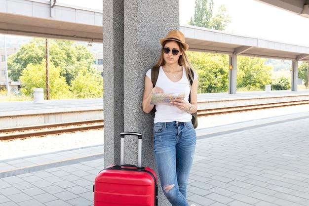 Donna alla stazione ferroviaria che punta sulla mappa
