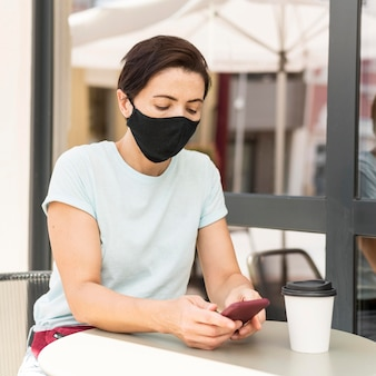 Donna alla terrazza indossando maschera