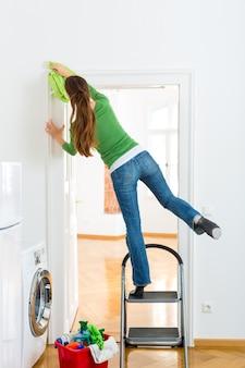 Donna alle pulizie di primavera che lavora pericolosamente