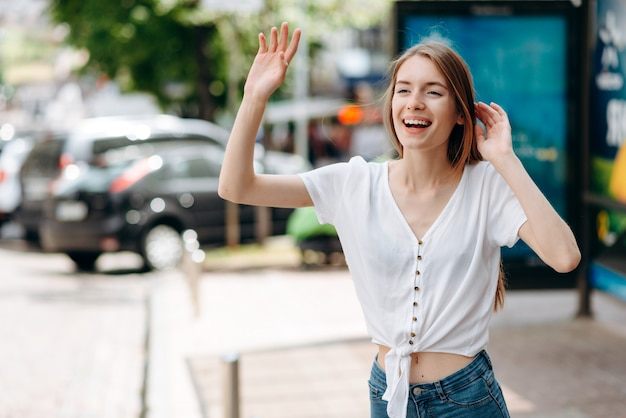 Donna allegra agitando la mano in piedi sul marciapiede onu per strada. gesticola ciao o prendi un taxi