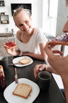Donna allegra attraente che esamina il suo uomo mentre mangiano prima colazione