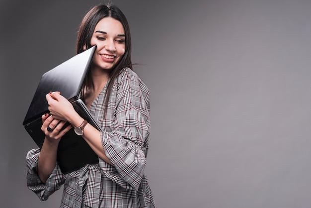 Donna allegra che abbraccia il computer portatile