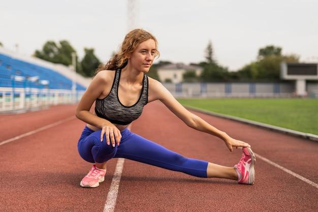 Donna allegra che allunga prima dell'allenamento