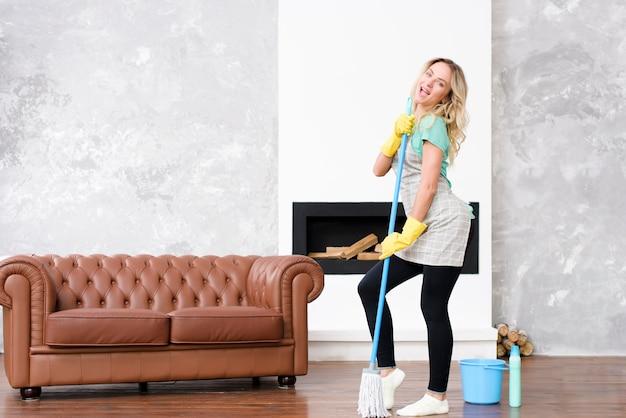 Donna allegra che balla con la scopa vicino al secchio e alla bottiglia del detersivo
