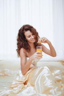 Donna allegra che beve un succo d'arancia che si siede sul suo letto a casa