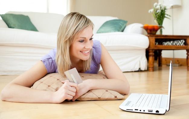 Donna allegra che compera online che si trova sul pavimento