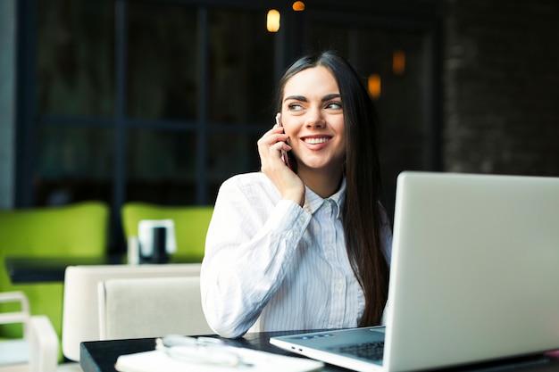 Donna allegra che comunica sul telefono al computer portatile