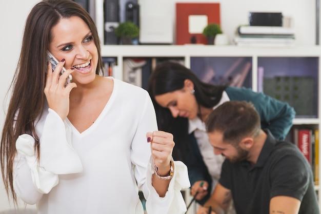 Donna allegra che comunica sul telefono e che celebra