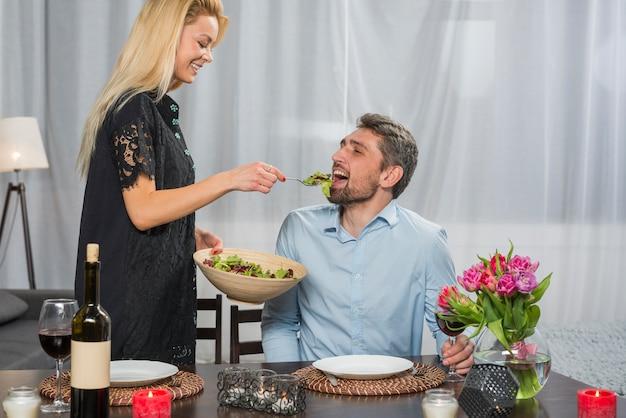Donna allegra che dà insalata all'uomo alla tavola