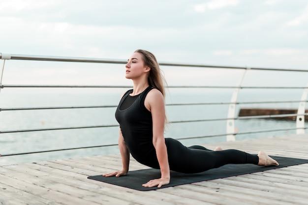 Donna allegra che fa asana di yoga sul mare di mattina