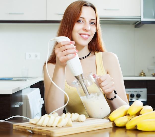 Donna allegra che fa scuotere il latte