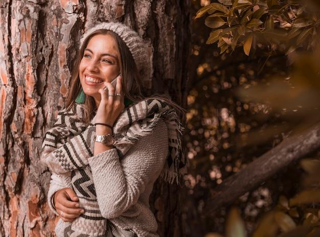 Donna allegra che ha conversazione telefonica vicino all'albero