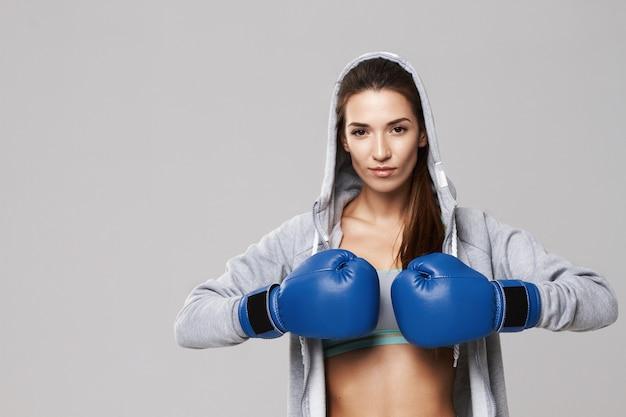 Donna allegra che indossa i guanti della scatola blu che si preparano sul bianco.