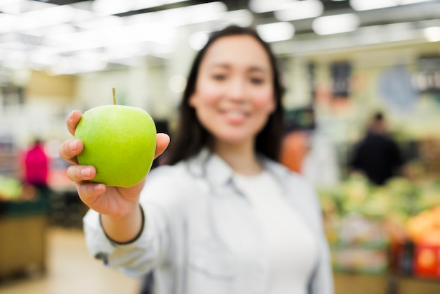 Donna allegra che mostra mela alla macchina fotografica