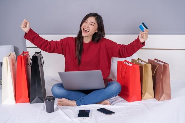 Donna allegra che per mezzo del computer portatile a comperare online sul letto