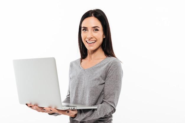 Donna allegra che per mezzo del computer portatile.