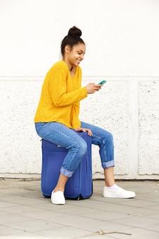 Donna allegra che per mezzo del telefono cellulare e sedendosi sulla valigia
