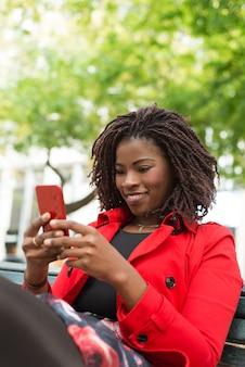 Donna allegra che per mezzo dello smartphone sulla via