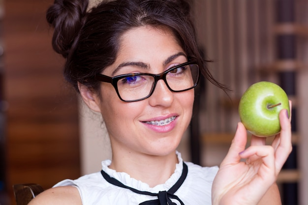 Donna allegra che propone con la sua mela