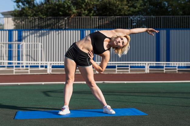 Donna allegra che scalda prima dell'allenamento