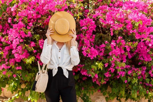 Donna allegra che si nasconde dietro il cappello di paglia