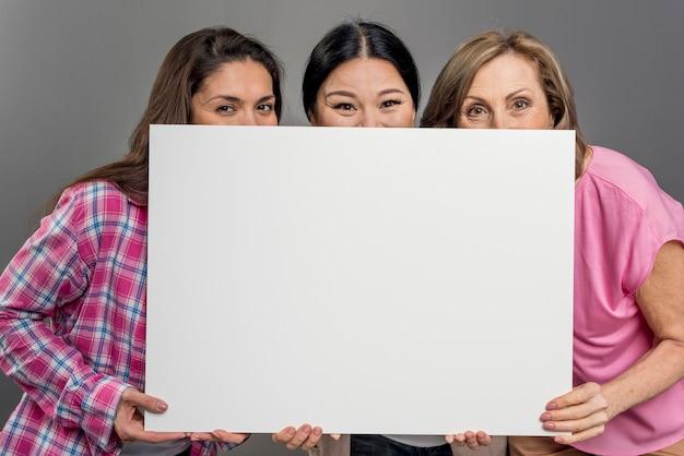 Donna allegra che si nasconde sotto il foglio di carta bianco