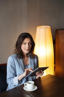 Donna allegra che si siede all'interno facendo uso del computer della compressa.