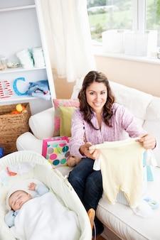 Donna allegra che si siede sul sofà con i sacchetti che legge una carta mentre il suo bambino sta dormendo nella sua culla