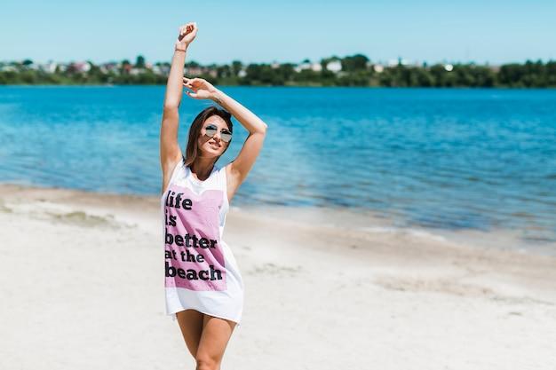 Donna allegra che si tiene per mano sulla spiaggia