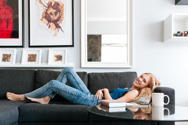 Donna allegra che si trova e che si rilassa sul sofà a casa