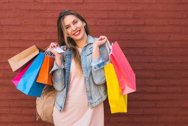 Donna allegra che sta con i sacchetti della spesa e la carta di credito al muro di mattoni rosso
