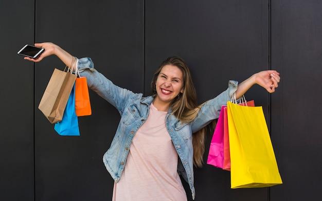 Donna allegra che sta con i sacchetti della spesa variopinti