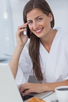 Donna allegra che telefona e che per mezzo del suo computer portatile