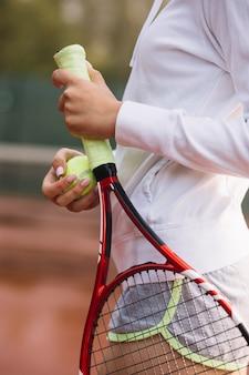 Donna allegra che tiene una racchetta da tennis con la palla