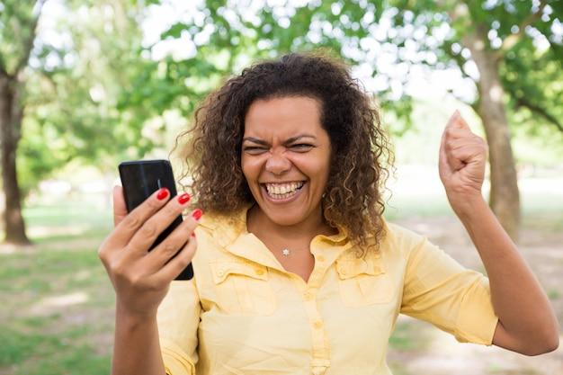 Donna allegra che utilizza smartphone nel parco della città
