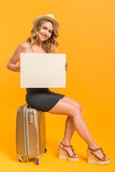 Donna allegra con carta bianca che si siede sulla valigia