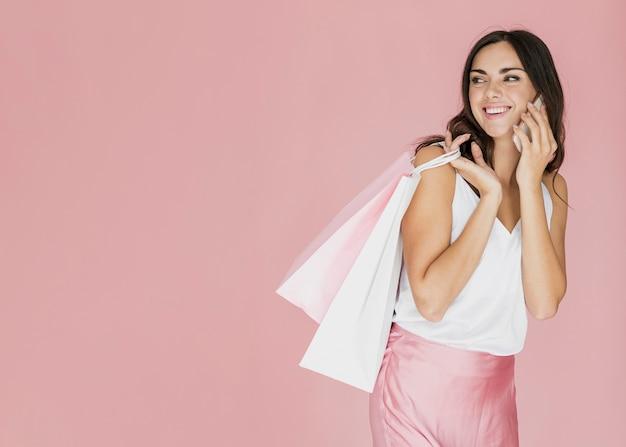 Donna allegra con i sacchetti della spesa che guarda indietro