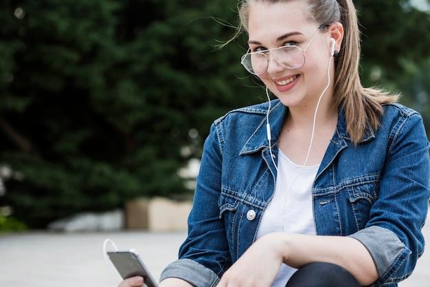Donna allegra con lo smartphone che si siede sul marciapiede