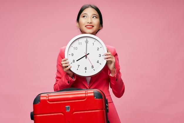 Donna allegra dell'aspetto asiatico che sorride tenendo un orologio con la valigia rossa